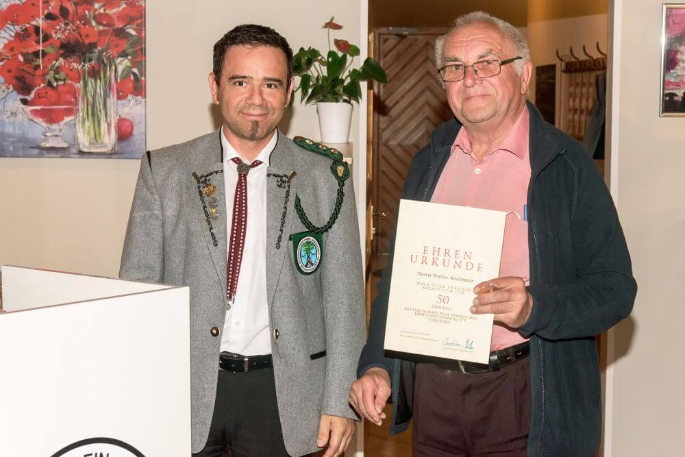 Über 50 Jahre im Verein und im BSSB ist Walter Kreitmair. Schützenmeister Laurent Boissat gratuliert und überreicht Ehrennadel und Urkunde.